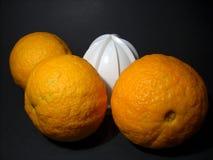 Sinaasappelen en juicer Stock Afbeelding