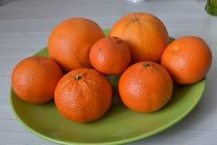 Sinaasappelen en mandarijnen op een groene plaat royalty-vrije stock fotografie