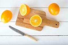 Sinaasappelen en op een houten raad op een witte houten achtergrond Royalty-vrije Stock Foto