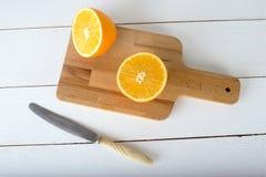 Sinaasappelen en op een houten raad op een witte houten achtergrond Royalty-vrije Stock Foto's