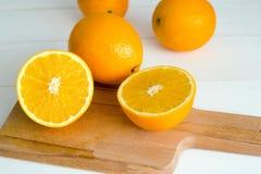 Sinaasappelen en op een houten raad op een witte houten achtergrond Stock Foto