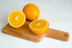 Sinaasappelen en op een houten raad op een witte houten achtergrond Stock Afbeeldingen