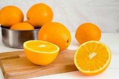 Sinaasappelen en op een houten raad op een witte houten achtergrond Royalty-vrije Stock Afbeeldingen