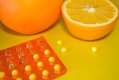 Sinaasappelen en vitamine C op gele achtergrond Stock Foto's