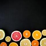 Sinaasappelen, grapefruit en citroen op zwarte achtergrond worden geïsoleerd die Vlak leg, hoogste mening Tropische de zomermenge Royalty-vrije Stock Foto