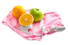 Sinaasappelen, groene appel, meetlint en roze kousen Stock Foto's