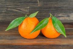 Sinaasappelen met bladeren op hout Stock Afbeelding