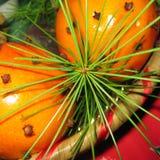 Sinaasappelen met pijnboombladeren en kruidnagels stock afbeeldingen
