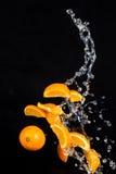 Sinaasappelen met waterplonsen op zwarte achtergrond royalty-vrije stock foto's