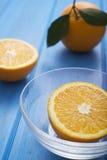 Sinaasappelen op een blauwe houten lijst Stock Afbeelding