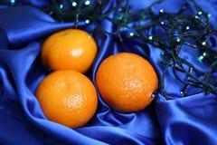 Sinaasappelen op een zijde blauwe stof Stock Foto