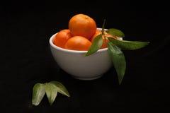 Sinaasappelen in witte kom op zwarte achtergrond Stock Foto