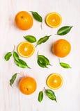 Sinaasappelenvruchten samenstelling met groene bladeren en plak Stock Fotografie