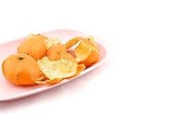 Sinaasappelschil op roze dienblad Royalty-vrije Stock Afbeeldingen