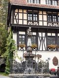 Fragment of the hotel Economat with statue of a bear sitting on a pole, located near Pelesh castle in Sinaia, in Romania Stock Images