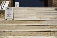 Sinais de aviso molhados do assoalho do cuidado em escadas Fotografia de Stock Royalty Free