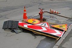 Sinais de estrada, cones do tráfego e boca de incêndio de fogo vermelho com mangueira Foto de Stock Royalty Free