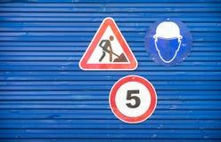 Sinais de estrada contra uma cerca azul do metal imagens de stock royalty free