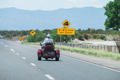 Sinais de estrada e motocicleta rodada três foto de stock