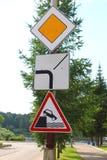 Sinais de estrada: estrada principal, o sentido da estrada principal, saindo da terraplenagem Foto de Stock