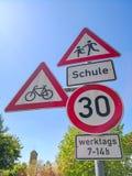 Sinais de estrada na frente do limite de velocidade da escola com meios alemães do texto: escola nos dias úteis 7-14h fotografia de stock