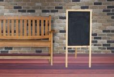 Sinais de madeira e cadeira de madeira situados na sala com parede de tijolo e Imagem de Stock