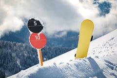 Sinais de número da inclinação e snowboard em montanhas fotografia de stock
