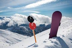 Sinais de número da inclinação e snowboard em montanhas imagens de stock