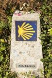 Sinais direcionais na maneira de St James Shell de vieira e seta amarela com fundo azul em uma parede Camino de Santiago Fotografia de Stock Royalty Free