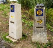 Sinais direcionais Shell de vieira e seta amarela com fundo azul em uma parede Camino de santiago, Espanha Foto de Stock Royalty Free