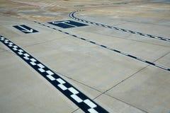 Sinais do assoalho da estrada de aeroporto pintados Fotografia de Stock Royalty Free