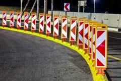 Sinais e refletores da estrada na estrada na noite fotografia de stock royalty free