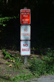 3 sinais em um polo: Mantenha nossos animais selvagens selvagens nenhuma não alimentação, nenhuma pesca, nenhumas bicicletas Foto de Stock