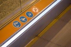 Sinais em uma escada rolante, sinais de aviso Fotos de Stock
