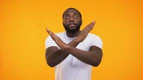 Sinal afro-americano da parada da exibição do homem novo com mãos, no fundo amarelo vídeos de arquivo