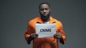 Sinal afro-americano do crime da terra arrendada do prisioneiro, olhando à câmera, conscientização video estoque