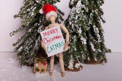 Sinal articulado de madeira CATMAS alegre da terra arrendada da boneca do manequim que veste a cena do inverno do chapéu de Santa imagens de stock royalty free
