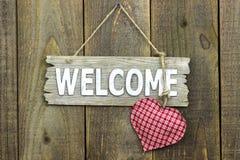 Sinal bem-vindo de madeira com o coração vermelho que pendura no fundo de madeira rústico Imagens de Stock Royalty Free