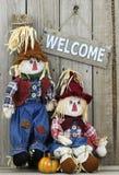 Sinal bem-vindo de madeira que pendura na cerca de madeira por espantalhos do menino e da menina Imagem de Stock