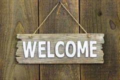 Sinal bem-vindo de madeira que pendura no fundo de madeira rústico Imagens de Stock