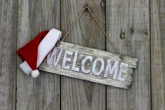 Sinal bem-vindo rústico com o chapéu de Santa Claus do Natal Imagens de Stock Royalty Free