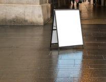 Sinal branco vazio do sanduíche fora no dia no passeio molhado escuro perto de uma construção imagem de stock