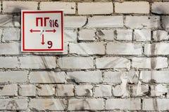 Sinal da construção contra uma parede de tijolo Fotografia de Stock Royalty Free
