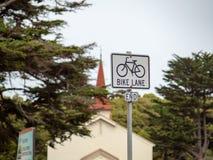 Sinal da extremidade da pista da bicicleta que entrega na frente de uma igreja fora imagens de stock