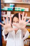 Sinal da parada de In Mask Gesturing do farmacêutico na farmácia Fotografia de Stock