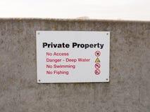 sinal da propriedade privada na barricada cinzenta da parede de mar nenhuma permissão fotografia de stock royalty free