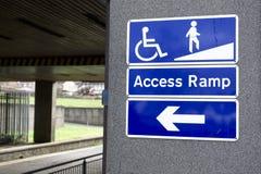 Sinal da rampa de acesso para a cadeira de rodas e a seta deficiente do sentido da rota fotos de stock