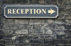 Sinal da seta das recepções na parede de tijolo Imagens de Stock