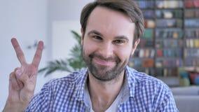 Sinal da vitória pelo homem ocasional da barba no escritório filme