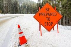 Sinal de aviso alaranjado em uma estrada nevado Fotografia de Stock Royalty Free